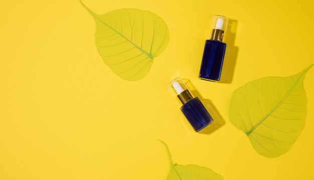 Szklane niebieskie butelki kosmetyczne z pipetą na żółtym tle. makieta marki kosmetyków spa, widok z góry
