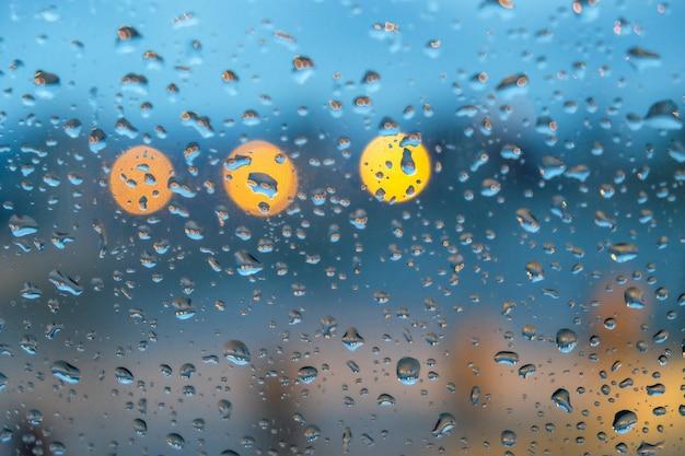 Szklane okno pokryte kroplami deszczu ze światłami na rozmytym tle