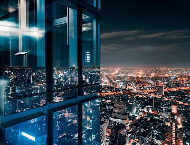 Szklane okno ze świecącym zatłoczonym miastem