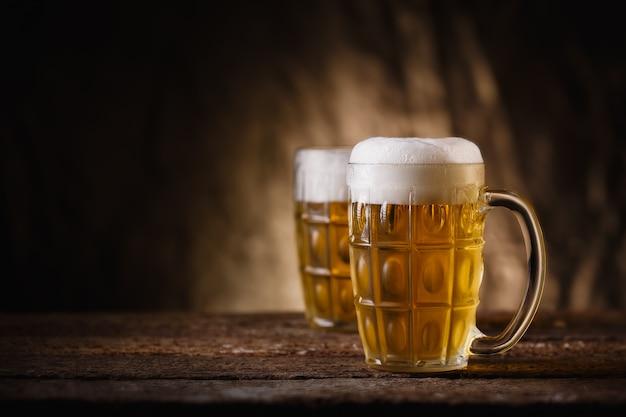 Szklane piwo na drewnianym tle z miejsca na kopię