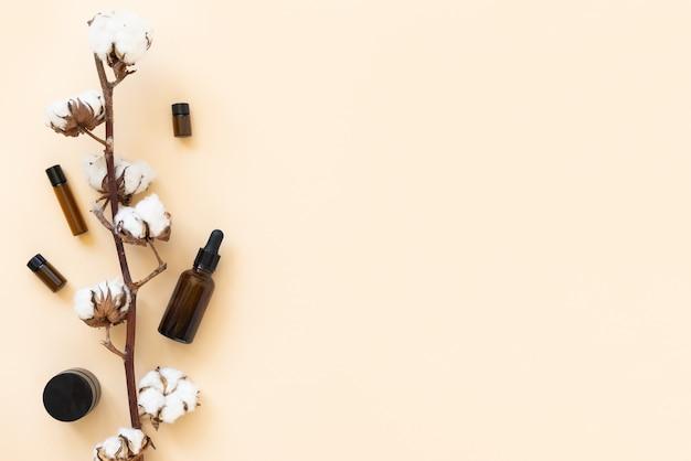 Szklane pojemniki na kosmetyki i olejki eteryczne z gałązką bawełny na beżowym tle