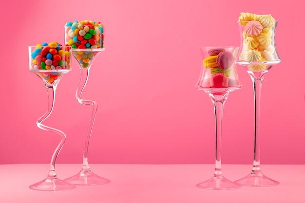 Szklane pojemniki z cukierkami i słodyczami na różowo