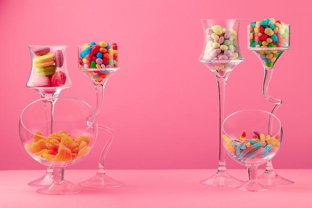 Szklane pojemniki z cukierkami i słodyczami na różowym tle