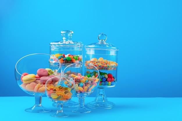 Szklane pojemniki z kolorowymi cukierkami na niebieskim tle