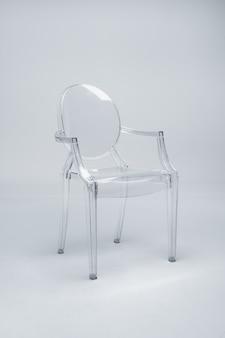 Szklane przezroczyste krzesło na białej ścianie. pojęcie minimalizmu