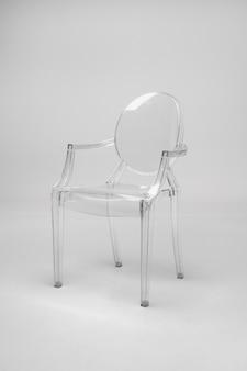 Szklane, przezroczyste krzesło na biało-szarej ścianie. pojęcie minimalizmu