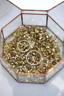 Szklane pudełko z obrączkami i złotymi cekinami