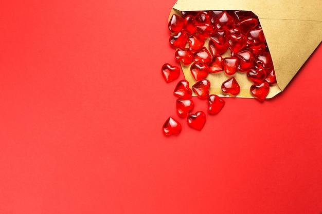 Szklane serca wylewają się z otwartej koperty na czerwonym tle.