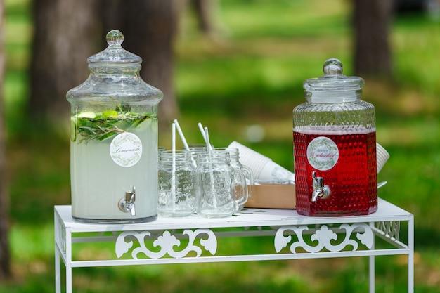 Szklane słoiki świeżej lemoniady na weselnym batoniku