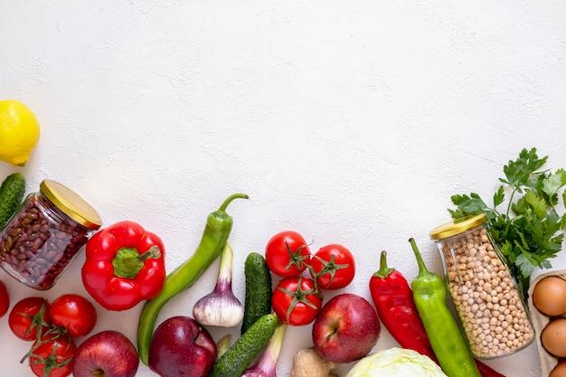 Szklane słoiki z ciecierzycy i fasoli oraz przyjazne dla środowiska warzywa i owoce