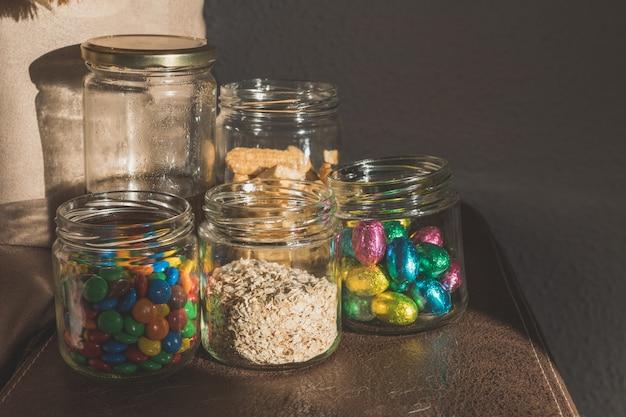 Szklane słoiki z czekoladowymi cukierkami, płatkami owsianymi, miodem, ciasteczkami i czekoladkami