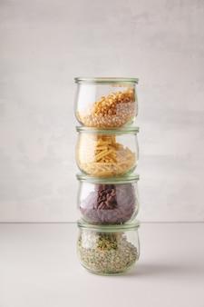 Szklane słoiki z makaronem, soczewicą, fasolą i kukurydzą