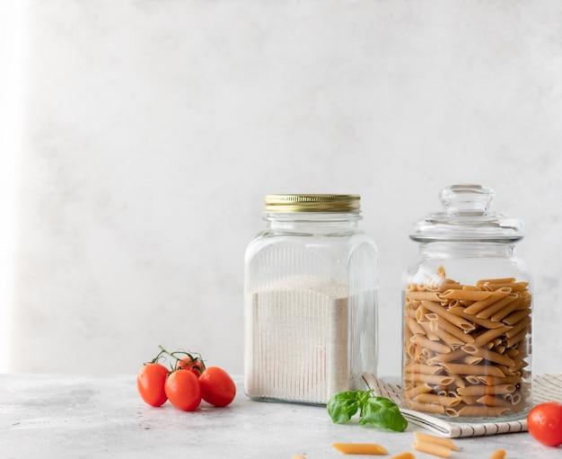 Szklane słoiki z pełnoziarnistą mąką i pełnoziarnistym makaronem penne. bezglutenowe