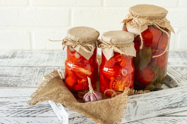 Szklane słoiki z pomidorami w puszkach z czosnkiem i pieprzem. fermentowane jedzenie na białym tle drewnianych.