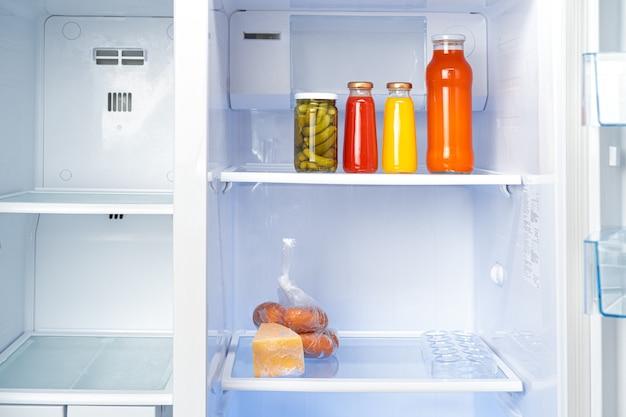 Szklane słoiki z produktami w puszkach na półce w lodówce