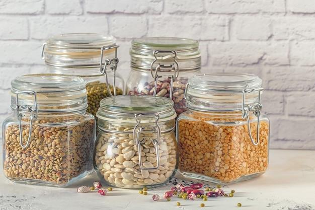 Szklane słoiki z różnymi roślinami strączkowymi - fasolą, fasolą mung, groszkiem i soczewicą. gotowanie, dieta, jedzenie wegańskie i wegetariańskie.