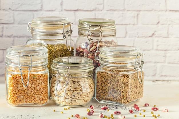Szklane słoiki z różnymi roślinami strączkowymi - fasolą, fasolą mung, groszkiem i soczewicą