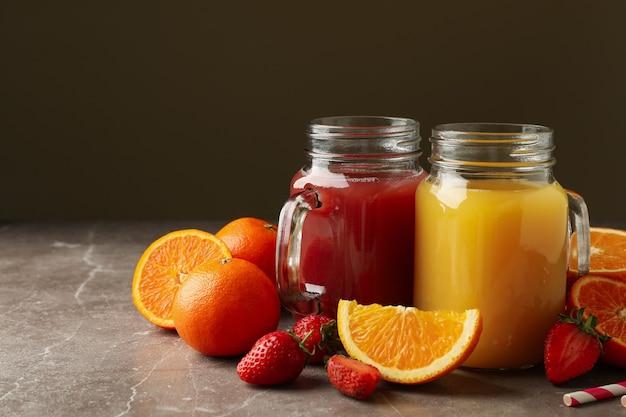 Szklane słoiki z sokami truskawkowymi i pomarańczowymi na szaro