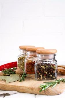 Szklane słoiki z suchymi przyprawami do gotowania na białym stole