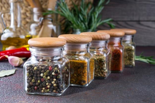 Szklane słoiki z suchymi przyprawami do gotowania na ciemnym stole