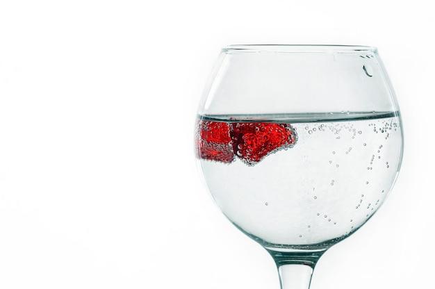 Szklanka cieczy na jasnym tle z czerwonymi kawałkami lodu. kawałki pokryte są pęcherzykami powietrza. tła i tekstury.