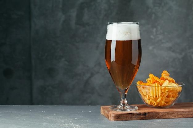 Szklanka ciemnego piwa z miską piwnych przekąsek z bliska