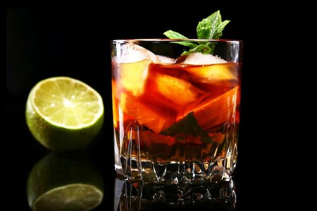 Szklanka ciemnego rumu koktajlowego z limonką, pomarańczą, kostkami lodu i liśćmi mięty.