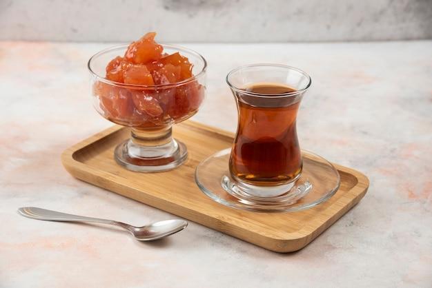 Szklanka czarnej herbaty i konfitury z pigwy na drewnianym talerzu.