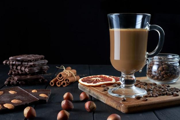 Szklanka czarnej kawy z mlekiem z czekoladą, orzechami laskowymi, laskami cynamonu i plasterkami suszonego grejpfruta