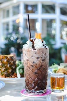 Szklanka czekoladowego koktajlu mlecznego z bitą śmietaną.
