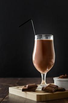 Szklanka czekoladowego koktajlu mlecznego ze słomką