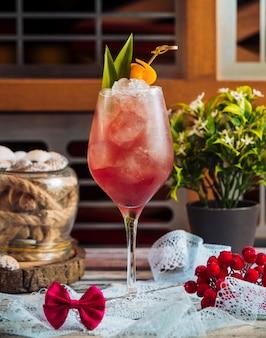 Szklanka czerwonego koktajlu z kostkami lodu i zielonymi liśćmi.