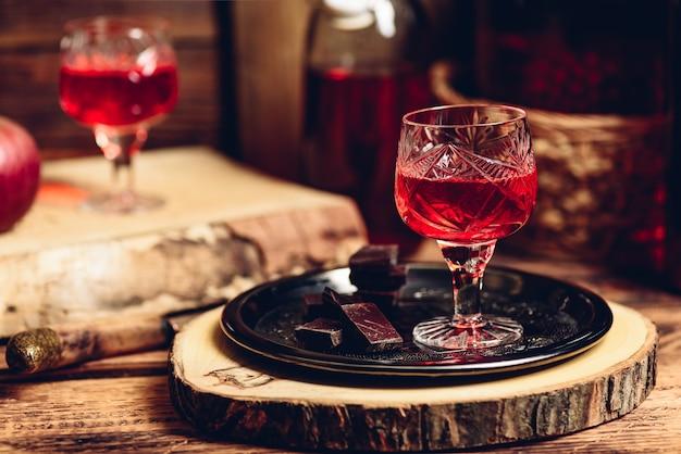 Szklanka czerwonego likieru z tabliczkami czekolady na metalowej tacy