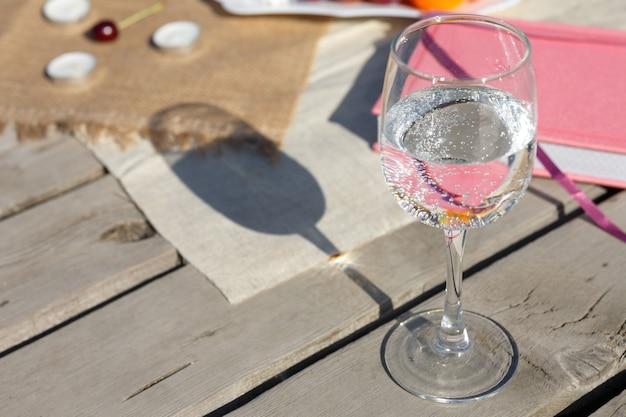 Szklanka czystej gazowanej wody mineralnej stoi na drewnianej podłodze ze starych desek