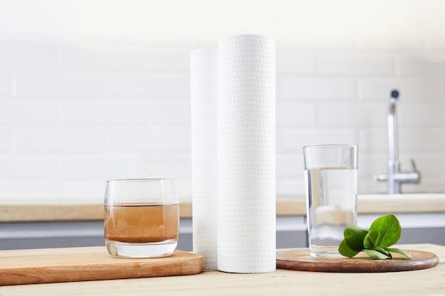 Szklanka czystej i brudnej wody z wkładami filtrującymi na tle domowej kuchni