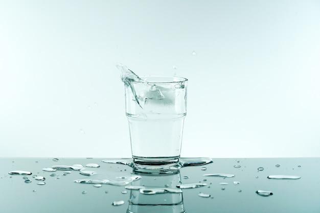 Szklanka czystej świeżej wody z kostką lodu.