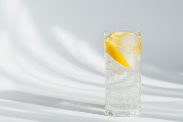 Szklanka czystej wody mineralnej gazowanej z lodem i cytryną na białej ścianie w słońcu. światło z twardymi cieniami i blaskiem ze szkła. śniadanie, świeży poranny drink