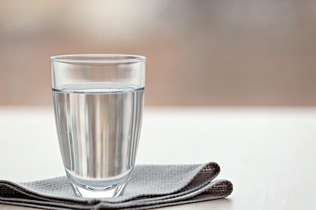 Szklanka czystej wody na rozmytym