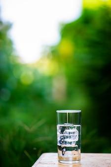 Szklanka czystej wody z lodem na stole gotowa do picia