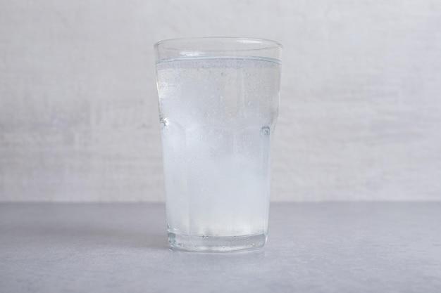 Szklanka czystej zimnej wody na szarym tle.