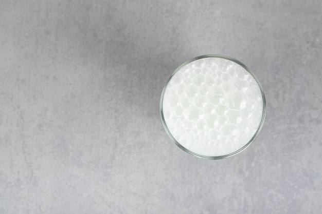 Szklanka czystej zimnej wody z bąbelkami na szarej powierzchni