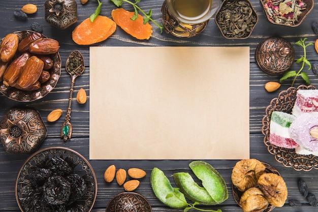 Szklanka do herbaty z różnymi suszonymi owocami, orzechami i papierem