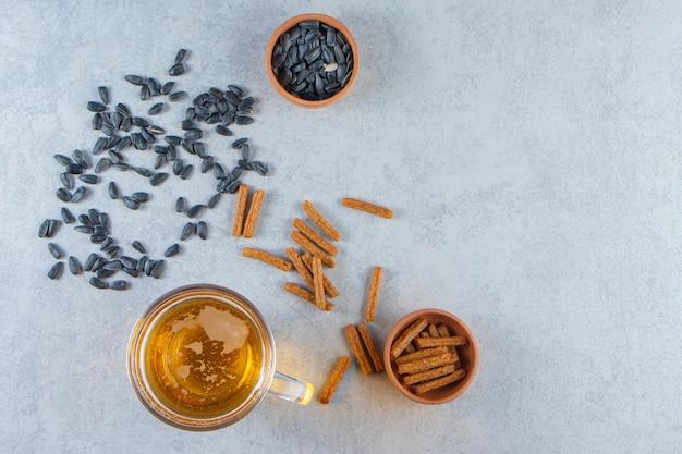 Szklanka do piwa i miska z grzankami z ciecierzycy, nasion, na marmurowym tle.