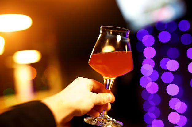 Szklanka do piwa z cienką nogą w dłoni.