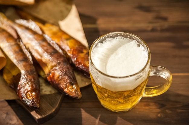 Szklanka do piwa z piwem i wędzoną na gorąco rybą