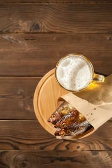 Szklanka do piwa z piwem i zbliżenie ryby wędzone na gorąco. piwny kubek z piwem i ryba na ciemnym tle i kopii przestrzeni.