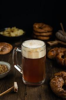 Szklanka do piwa z preclami, kiełbaską i przekąskami na rustykalnym drewnianym stole