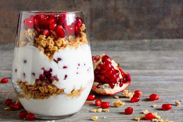Szklanka domowego jogurtu parfait z granolą i granatem fr