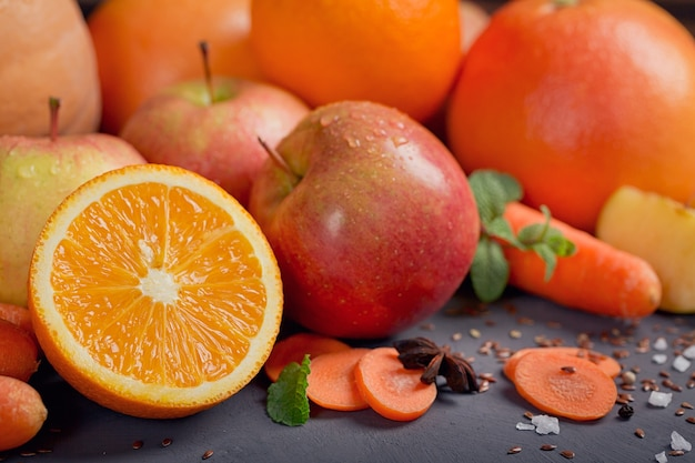 Szklanka domowego soku lub koktajlu, owoców i warzyw. świeża marchewka, jabłko, dynia, pomarańcza, grejpfrut na ciemnym stole. zdrowe odżywianie, jedzenie, dieta, detoks i koncepcja wegetariańska.