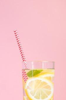 Szklanka domowej lemoniady z cytryn, mięty i czerwonej papierowej słomy na różowym tle. letni orzeźwiający napój.